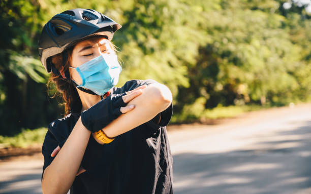 cyclist woman looking at her left elbow that has a road rash